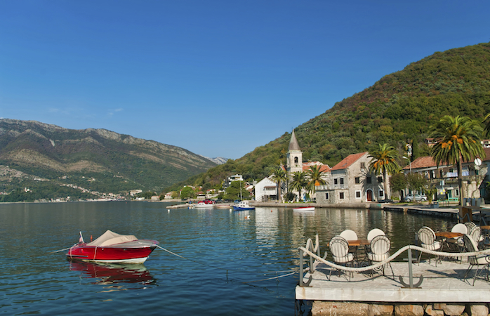 seafront restaurant and Church of Saint Roch at the back, Tivat, Montenegro