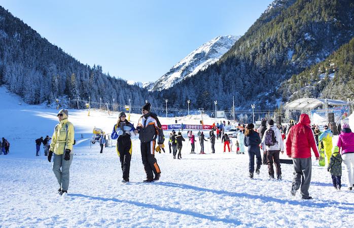 Bansko, Bulgaria - December, 12, 2015: Ski resort Bansko, Bulgaria, pistes and mountain with pine trees, ski slope, people walking and skiing