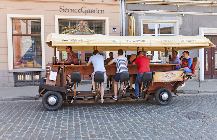 Riga, Latvia - May 25, 2014: Partybus Beer Bike with bar attendants on the street of Riga, Latvia. It is a pedal powered bar on the wheels. As the bar attendants pedal the barman is steering